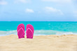 Tropical summer beach background. Pair of sandals on a white sand beach.