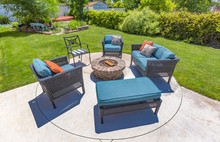 Chairs Around A Circular Fire Pit In The Backyard