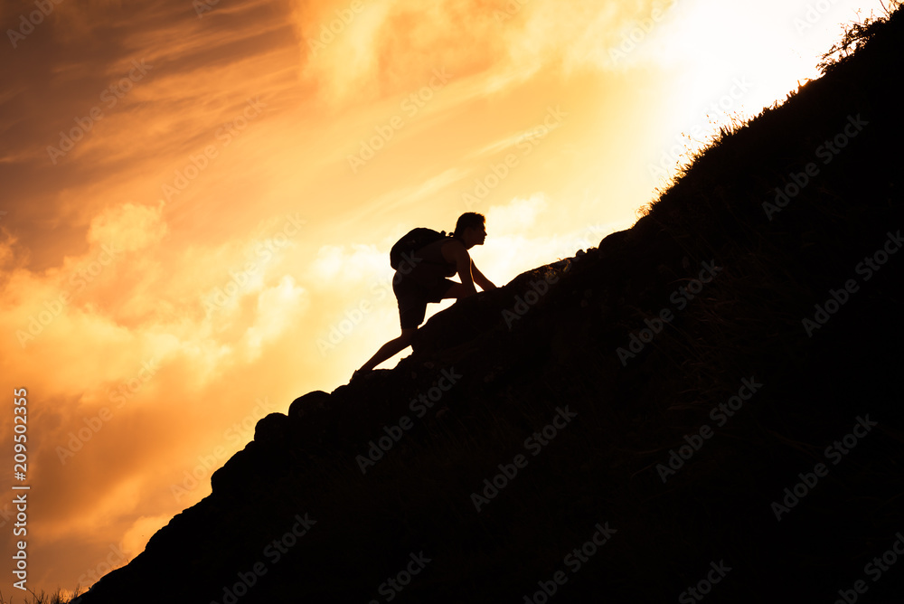 Fototapeta Man hiker climbing up a steep mountain cliff.  People taking risk, motivation and outdoor adventure concept.