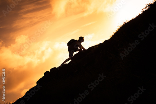 Fotografie, Obraz  Man hiker climbing up a steep mountain cliff