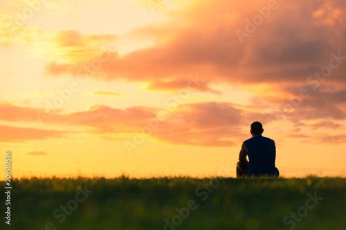 Photo Alone man watching the sunset.
