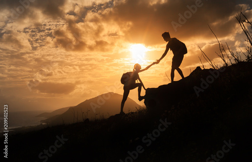 Fototapety, obrazy: People helping each other up a mountain. Adventure, taking risk,  and teamwork concept.