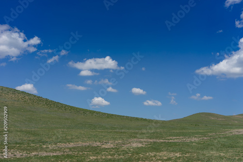 Natural landscape with hills on blue sky background.