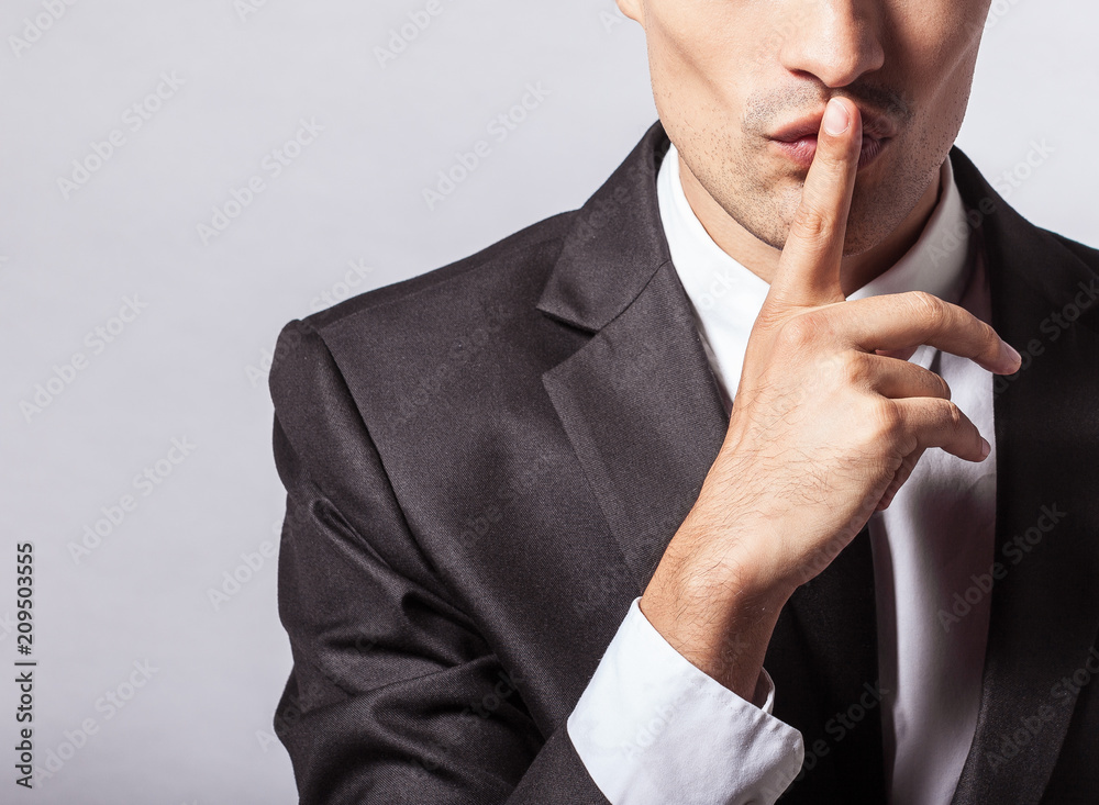 Fototapeta Man saying hush be quiet with finger on lips gesture isolated on gray wall background. Top secret concept.