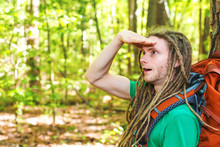 Male Hiker With Backpack Looking At Something Ahead In The Forest