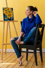 Girl Artist Sitting On Chair In Sweater And Jeans. She Is Barefoot And With Dirty Face In Paint. In Background Picture With Sunflowers On Easel. Creative Profession.
