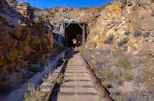 Train Tracks Leading To Tunnel In Desert