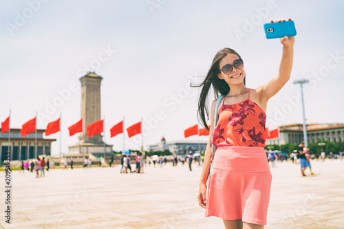 Foto op Canvas Aziatische Plekken Asian woman taking selfie photo with phone in Beijing, China. Asia travel. Tourist girl sightseeing famous sight holding mobile smartphone visiting Tiananmen Square. Summer vacation.