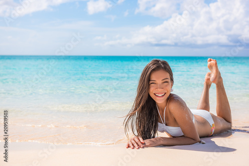 Asian bikini model woman relaxing sunbathing on white sand on paradise beach tropical travel, blue ocean background. Travel holiday girl relaxing on Caribbean beach summer vacation.