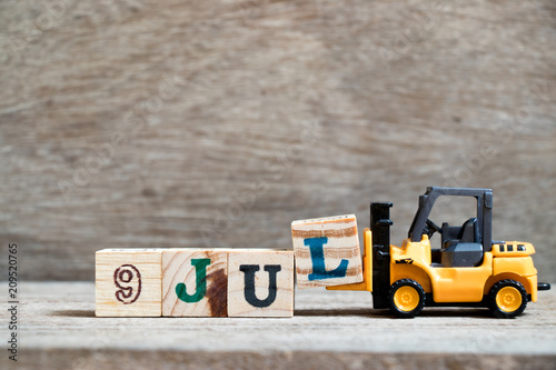 Poster  Toy forklift hold block l to complete word 9 jul on wood background (Concept for