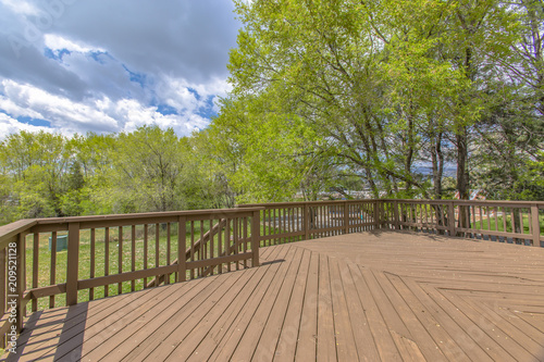 Photo  Wooden deck with cloudy skies and green trees