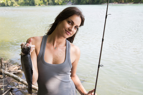 Fishing woman with fresh caught trout Canvas Print