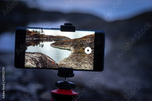 The phone is on a tripod. The phone shoots a video. Rocky shore. Photography of wild nature. Protocols between the islands. Journey to the wild.