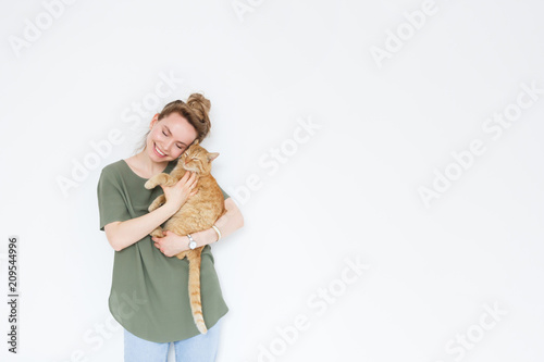 Obraz na plátně portrait handsome young hipster woman, hugs his good friend ginger cat on white wall background