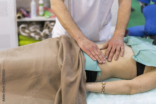 Physiotherapist doing shoulder massage to patient in a medical office Poster