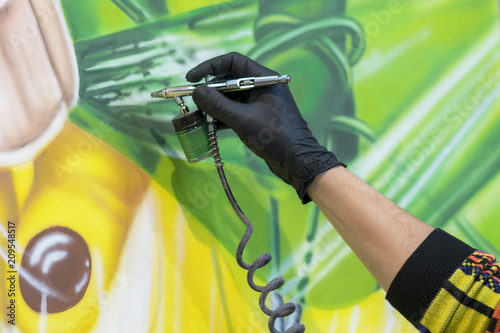 The artist paints a picture with a spray gun Wallpaper Mural