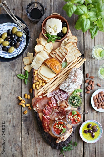 Fototapeta      Mediterranean appetizers table concept. Dinner table with tapas selection: cured meat and salami, gazpacho soup, jamon, olives, cheese, hummus and vegetables. Overhead view. obraz