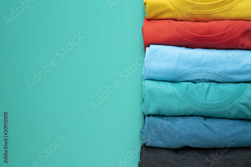 Valokuva  close up of rolled colorful clothes on green background