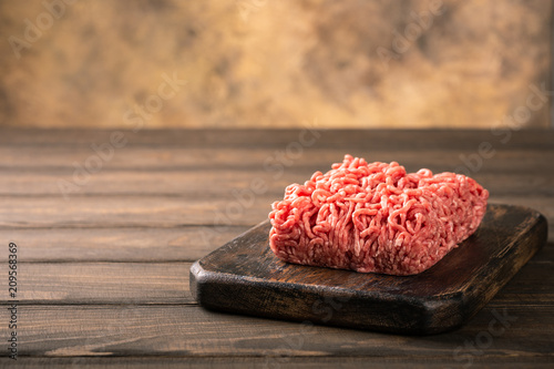 Fresh raw beef minced meat on dark wooden board. Healthy food ingredients concept with copy space.