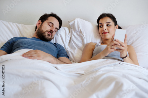 Cheating wife using mobile phone lying in bed next to his sleeping husband Fototapete