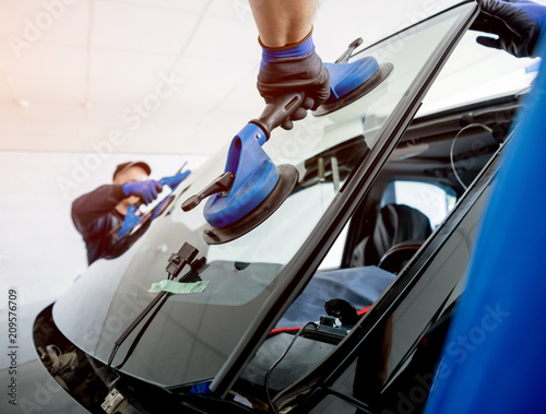 Automobile special workers replacing windscreen or windshield of a car in auto service station garage. Wall mural