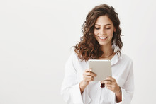 Charming Cute Caucasian Woman In White Trendy Blouse Browsing In Net Via Tablet, Smiling And Expressing Happiness, Standing Against Gray Background. Fashionable Woman Editing Her Photos In App