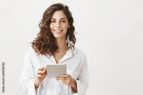 Photo Successful caucasian woman in trendy blouse holding tablet and smiling cheerfully at camera, expressing confidence while standing against gray background