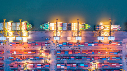 Fototapeta Container ship in export and import business and logistics. Shipping cargo to harbor by crane. Water transport International. Aerial view and top view.
