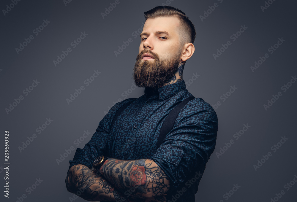 Fototapeta Handsome old-fashioned hipster in shirt and suspenders, pose with crossed arms. Isolated on a dark background.