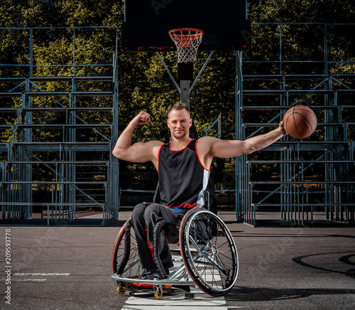 Cuadros en Lienzo Smiling cripple basketball player in wheelchair holds a ball on open gaming ground