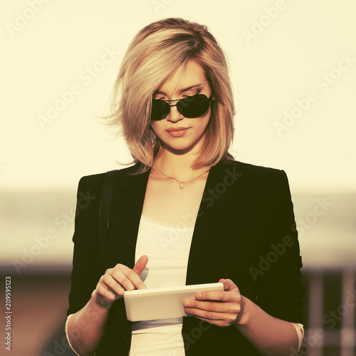 Tela Young fashion business woman in sunglasses using tablet computer in city street