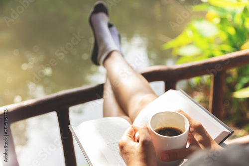 Photo Happy Woman sitting and holding cup of hot coffee.