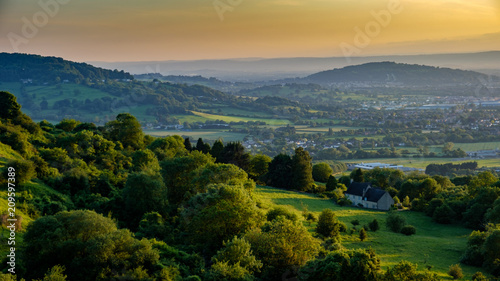 Photo  View of a farm house from Crickley Hill looking west with hills in the background and a yellow sky from the sunset