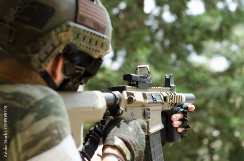 Fotomural  Special forces soldier red dot sight green background forest