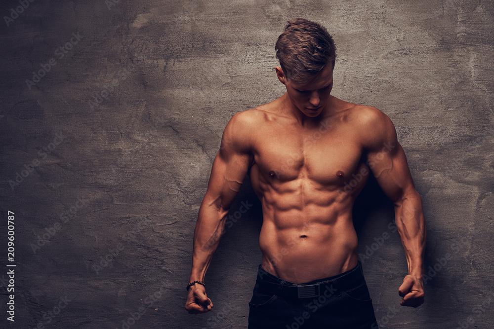 Fototapeta Beautiful shirtless young man model with nice muscular body posing at a studio.