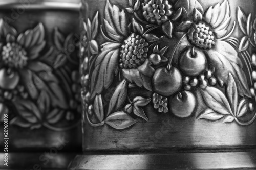 Photo Details of an old metal cup holders, decorated with a bas-relief depicting leave