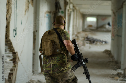Fotografía  Soldier walking inside building hold down rifle