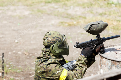 Paintball player in protective uniform and mask aiming gun in the forrest cover Canvas Print