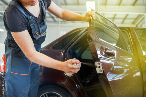 Fotomural Mechanic lubricates the car, repairs the car door, lubrication spray