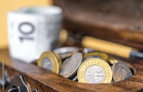 Fotografía  Vintage wooden box full of money: rolled up Polish zloty banknotes and coins in a chest on wooden surface