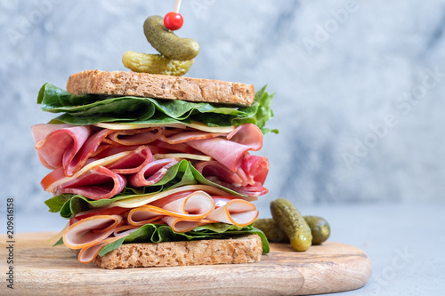 Fototapeta Big sandwich with ham, deli meat and vegetables obraz