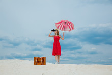 Young Woman In Red Dress With Umbrella And Suitcase Looking In Binoculars On The Beach. Travel Concept Image On Sand