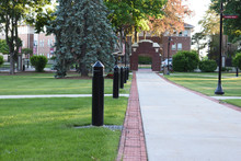College Campus Walkway Leading To Entrance Archway With Lights At Dusk.