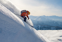 Skier Rides Freeride On Powder Snow Down Slope Against The Backdrop Of The Mountains