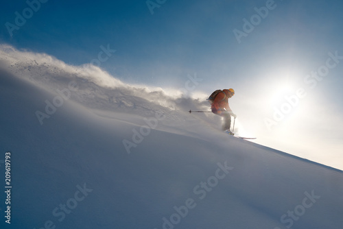 Fotografija skier rides freeride on powder of snow leaving wave