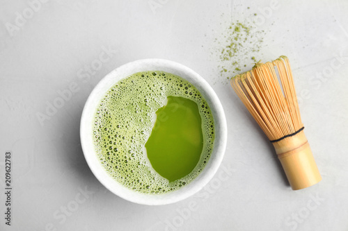 Chawan with fresh matcha tea and chasen on grey background, top view