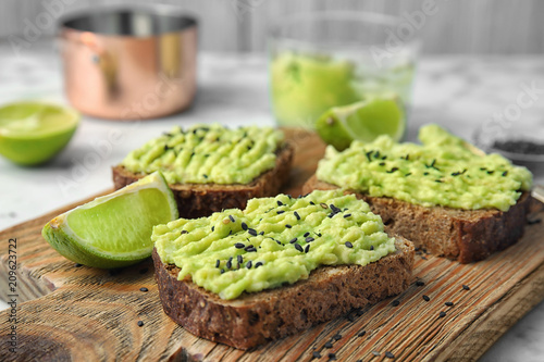 Crisp rye toasts with avocado on wooden board, closeup