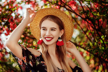 Young Beautiful Happy Smiling Girl With Red Lips, Long Blonde Hair, Wearing Straw Hat, Long Tassel Earrings, Cold Shoulder Dress, Posing Near Blooming Tree