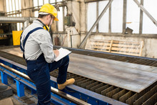 Serious Concentrated Factory Inspector Leaning By Foot On Conveyor Belt And Analyzing Quality Of Metal Sheer On Rolling Mill In Shop While Making Notes