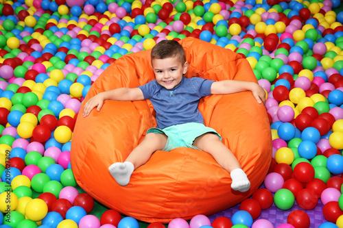 Photo Cute boy on beanbag in entertainment center